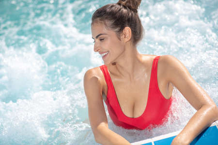 Holiday time. Beautiful female with bun swimming in pool in red swimming suit