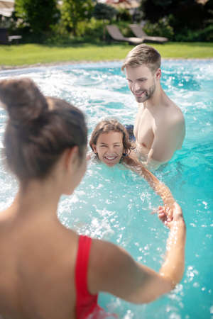 Family holiday. Excited parents teaching swimming to their son in the pool