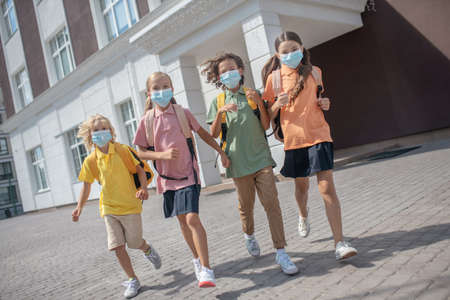 After lessons. Schoolchildren in protective masks on their way home after lessons