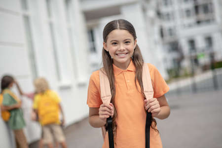 After school. Cute girl in orange tshirt smiling nicely and feeling good