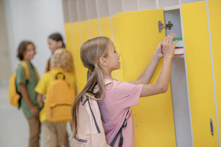 After lessons. Pretty girl in pink tshirt putting books to her locker