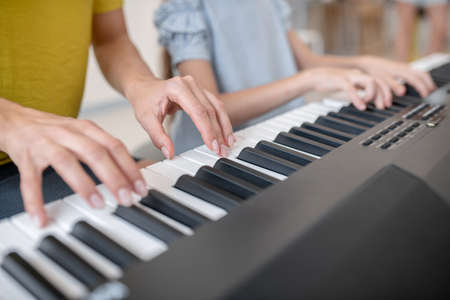Together. Close up picture of two people playing piano together