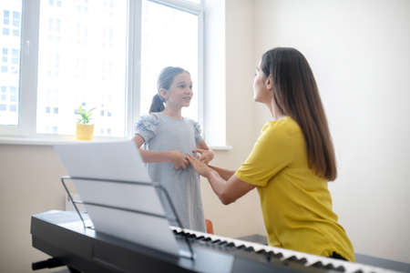 Music school. Girl and her teacher communicating at the lesson Imagens