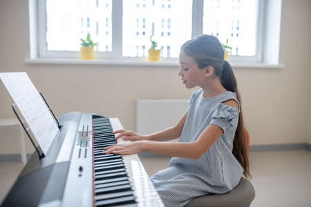 Playing the piano. Long-haired girl in blue dress sitting at the piano
