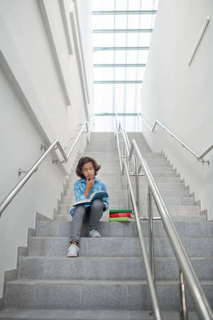 School time. Concentrated schoolboy sitting on stairs, reading book, holding his chin