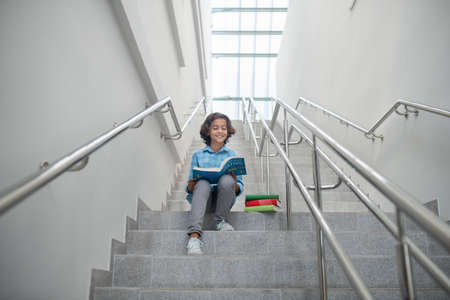 School time. Pleased schoolboy sitting on stairs, reading book, getting ready
