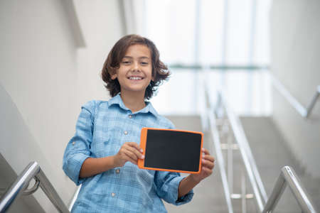 Joyful mood. Joyful smiling school-age boy in light blue shirt showing tablet screen standing on stairs
