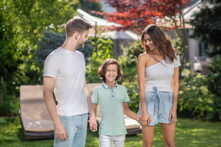 Family time. Family of three holding hands, smiling, looking at each other