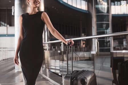 Elegant traveller. A woman wearing a black dress while having a business trip