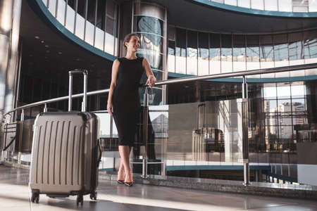 Convenient travelling. A woman waiting for the departure in a modern airport building