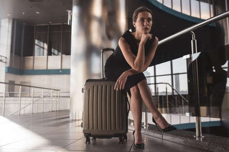 In the airport. A woman sitting on a suitcase while waiting for a flight