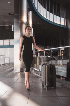 Confident business lady. A woman wearing a black dress while having a business trip 免版税图像