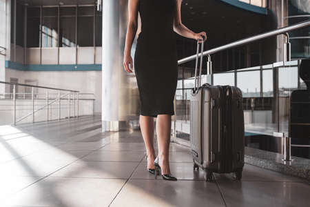 Travelling for business. A woman walking through a railway station with a suitcase 免版税图像