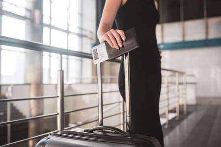 Travel details. A young beautiful woman holding a boarding pass and a suitcase 免版税图像