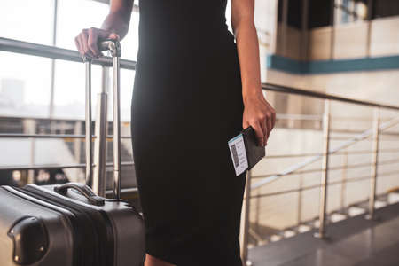 Getting ready for a business trip. A woman wearing a black dress in the airport