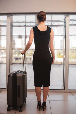 Stylish trip. A woman wearing heels travelling with a large suitcase