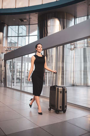 Before the trip. A confident woman with a suitcase arriving to the airport