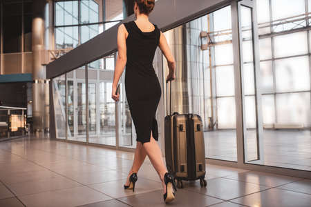 Luggage. A woman wearing a black dress and carrying a suitcase