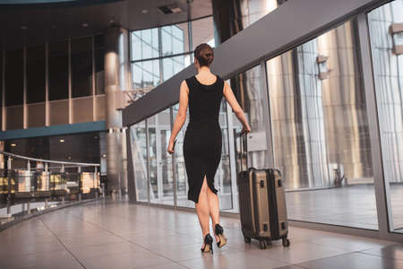 Being confident. An elegant woman walking through the airport with a suitcase 免版税图像