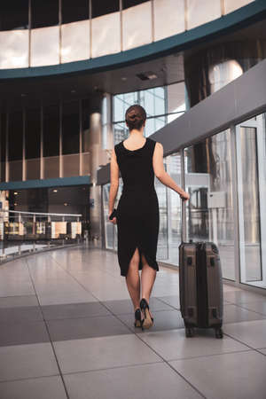 Woman with a suitcase. A woman wearing a black dress while having a business trip