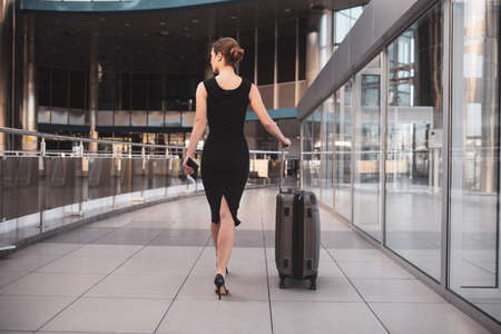 Looking for a right gate. An elegant business lady walking through the airport terminal 免版税图像