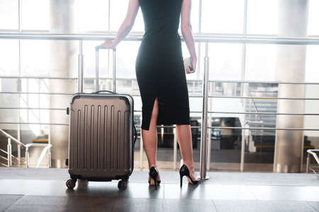 Personal luggage. An elegant woman holding a large plastic suitcase