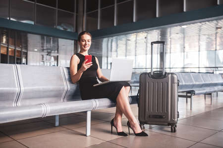 Business trip. A business woman managing tasks while waiting for a flight