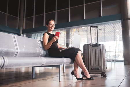 Communication. A business lady dealing with urgent tasks before a flight