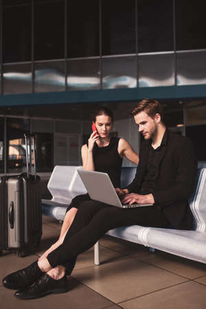 Free wi-fi. A man and woman using gadgets in the airport
