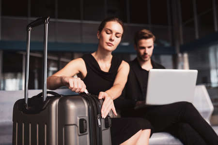 Checking necessary details. A concentrated woman opening a large brown suitcase