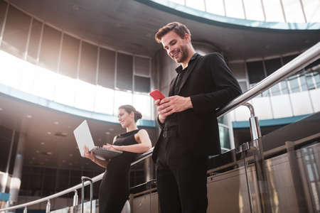 Staying connected. A man and woman using airports wi-fi for communication
