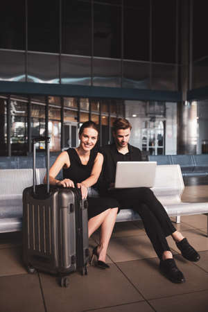 Wearing black clothes. Man and woman waiting for a flight together