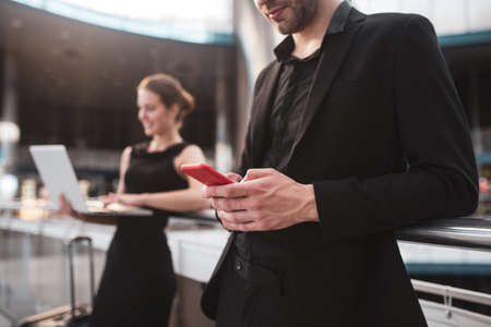 Texting. An officially dressed man typing a message on a smartphone