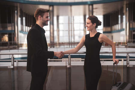 Shaking hands. Male and female business partners meeting each other in the airport