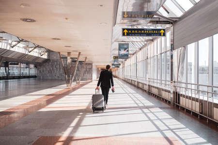 Having a flight. Man carrying his luggage through the airport terminal 版權商用圖片