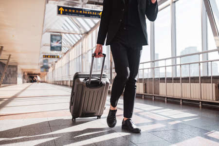 Business trip. A man carrying his suitcase through the railway station
