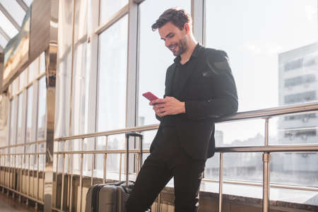 Free internet. A man texting with his friends in the airport
