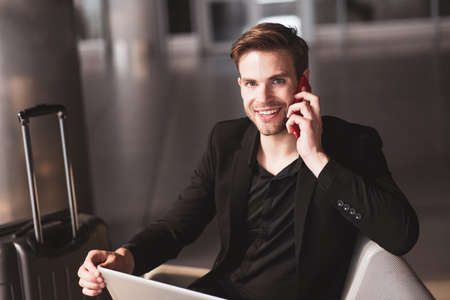 Working communication. A smiling man having a phone conversation while working