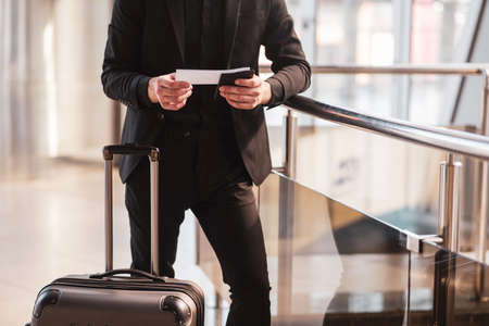 Boarding. A man checking travel details in his boarding pass 版權商用圖片