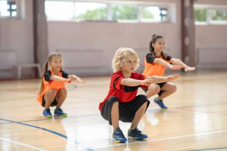 Squats. Three kids exercising in the gym and doing squats Imagens