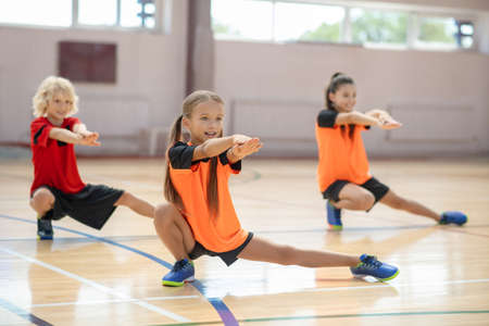 Strong legs. Three kids exercising in the gym and doing lungings to the left