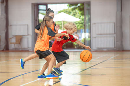 Basketball. Kids in bright sportswear playing basketball together and feeling excited