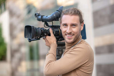 Filming process. Smiling fair-haired operator standing with camera on his shoulder outside
