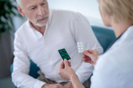 Medical treatment. Blonde female doctor giving two blister packs with pills to gray-haired male patient