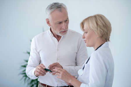 Medical treatment. Gray-haired male patient holding pill blister pack, consulting with blonde female doctor 版權商用圖片