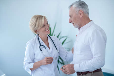 Medical treatment. Smiling blonde female doctor holding pill blister pack, patting gray-haired male patient 版權商用圖片