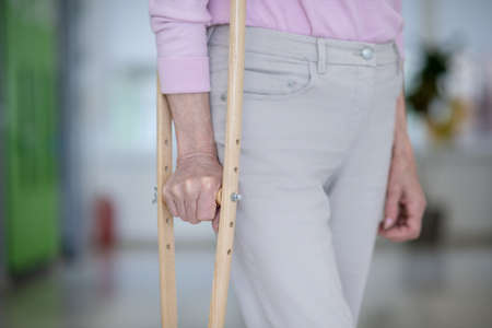 With a crutch. Close up of elderly woman with a crutch