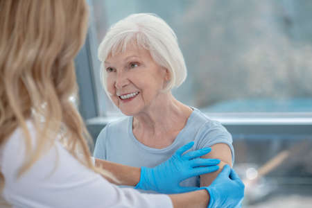 Vaccination. Long-haired female nurse making vaccination to an elderly woman