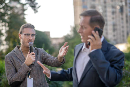 Unpleasant questions. Mature man speaking on the phone, unwilling to give interview to male journalist Archivio Fotografico