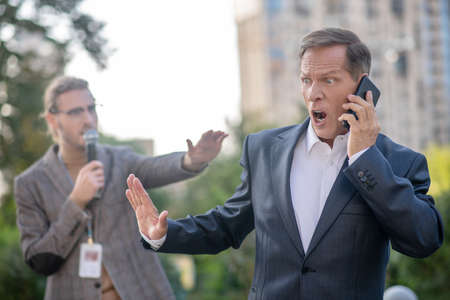 Unpleasant questions. Mature man speaking on the phone, pushing male journalist away, yelling